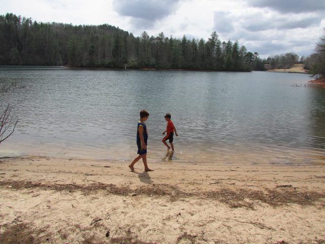 Boys wading Lake Keowee - The Family Glampers